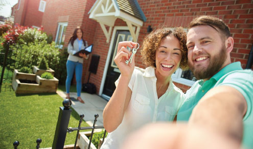 Couple taking selfie with new home